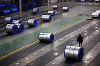 A worker walks through newly made rolls of steel sheets at Ma Steel's new plant in Maanshan, China.<br /> 29 Dec 2008