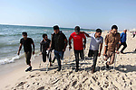 Wounded Palestinians, who were lose their legs during the clashes with Israeli troops, walk on the beach of Gaza city on May 29, 2019. Photo by Mahmoud Ajjour