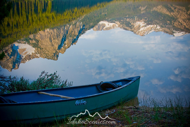 A green canoe on the shore of Stanley Lake with Mt. Mc Gown of the Sawtooth Range reflected in the calm morning water.