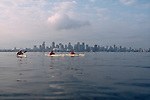 Vancouver, British Columbia, Canada, sea kayakers cross Burrard Inlet, city skyline, 2002, model released,