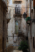 In the old part of the town of Taranto, the view of a suggestive alley, with the partially broken windows and balconies on the wall of the old building in the background, a cable that crosses it, a street-lamp, and some bed sheets or curtains that were spread out to dry in the air.  One of the window on the (once rose colored) brick wall in the background is partially still reflecting and partially bricked over. Digitally Improved Photo.