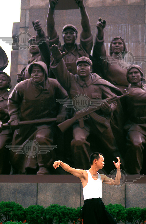 ©Mark Henley/Panos Pictures..China, Liaoning (Manchuria), Shenyang..Man performing Tai chi exercises in early morning in front of monumental socialist statue in city centre, a remnant of the days when the now ailing city was an industrial  powerhouse of the socialist state.