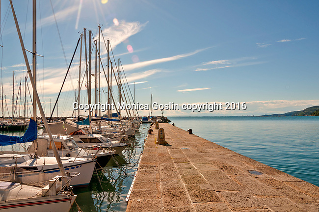 Pier and boats docked at Trieste Grignano with a view of the Gulf of Trieste, Italy