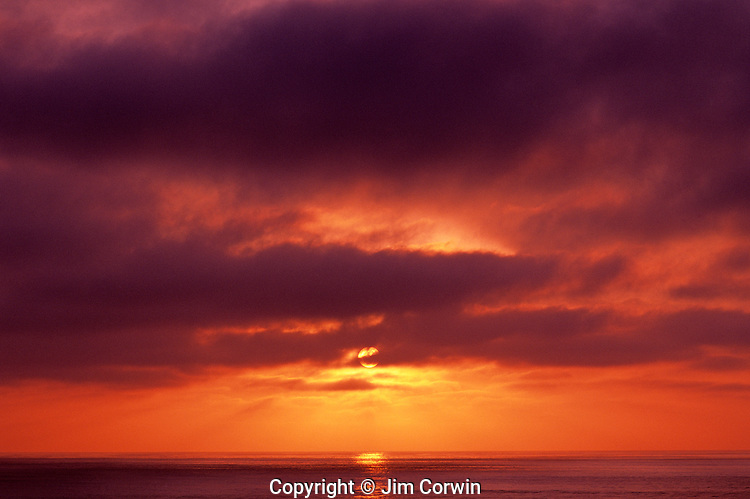 Storm clouds off the California Coast at winter time with sun breaking through clouds at sunset San Diego California USA..
