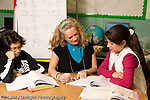 Education Elementary school Grade 5 female teacher working with female student male student reading looking left out or disgruntled ignored nearby horizontal