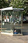 Sleeping in a Parisian telephone box. Paris, France.