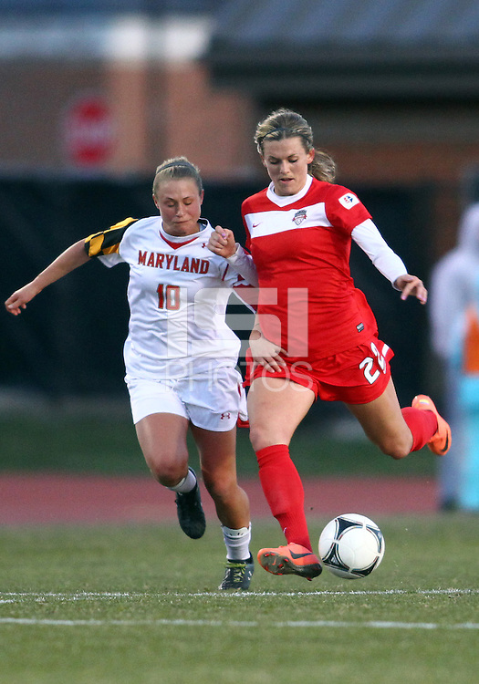 COLLEGE PARK, MARYLAND - April 03, 2013:  Stephanie Ochs (22) of The Washington Spirit keeps the ball away from Riley Barger (10) of the University of Maryland women's soccer team in a NWSL (National Women's Soccer League) pre season exhibition game at Ludwig Field in College Park Maryland on April 03. Maryland won 2-0.