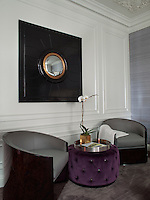 The bedroom is furnished with a pair of Art Deco style tub chairs upholstered in classical grey and an aubergine buttoned ottoman