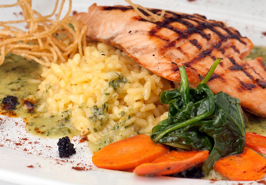 Grilled Salmon over a bead of yellow risotto rice and legumes.