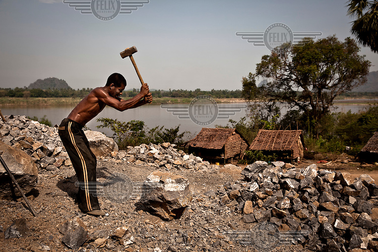 A man breaking and collecting rocks on the banks of the Salween River for use in as construction aggregate. Kayin state's unique limestone formations, which typify the landscape and are key to tourism in the area, have been eyed for future cement production, with approximately 10 limestone mining operations underway and another four exploration licenses granted.