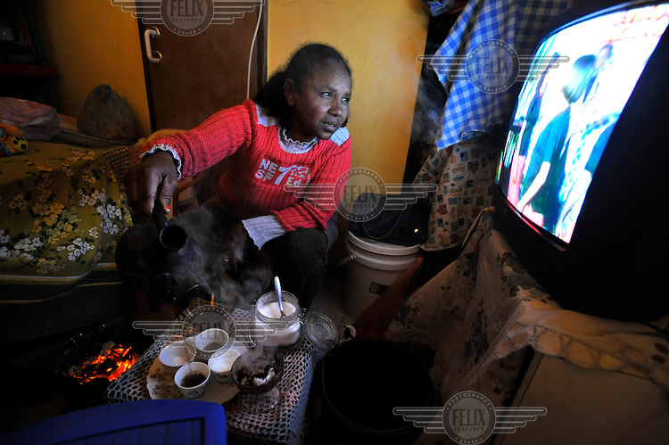 A woman pours coffee as she watches TV, sitting at her room in a compound of Eritrean asylum seekers.