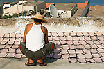 Man curing leather on a roof top, Essaouira, Morocco