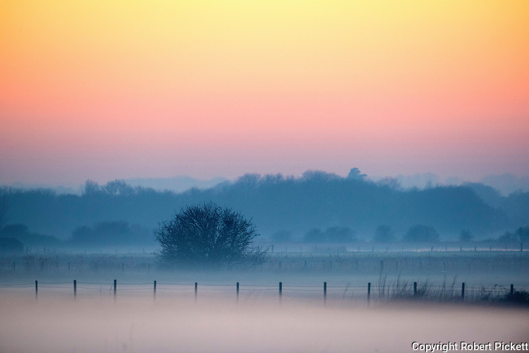 Sunset sky, view over farmland with evening mist and setting sunlight, Sandwich Kent UK