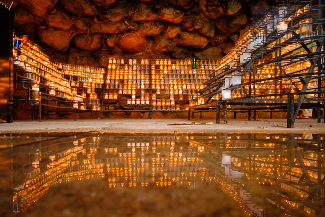 July 21, 2016; Grotto candles reflected in a puddle. (Photo by Matt Cashore/University of Notre Dame)