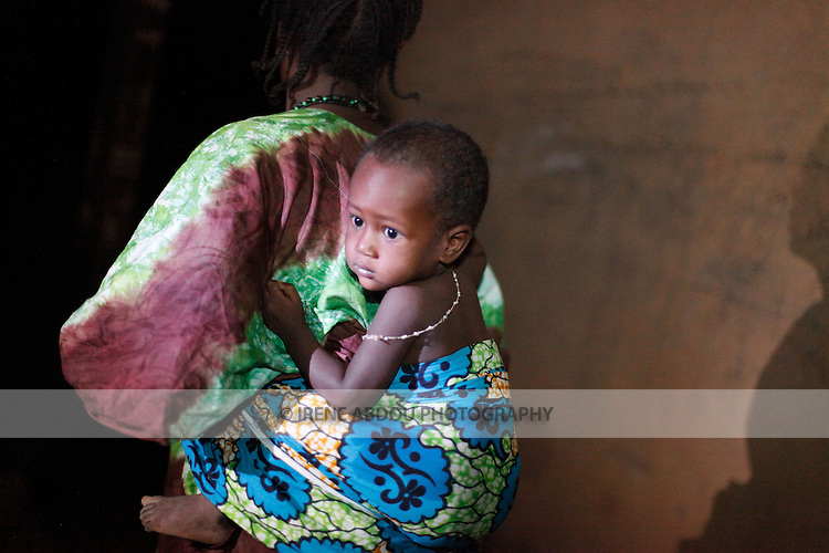 As night falls over the town of Djibo in northern Burkina Faso, a woman straps her child to her back.