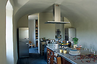 The long kitchen island which is filled with drawers dominates the barrel-vaulted kitchen