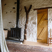 An African Dogon ladder is a dramatic focal point of the guest bedroom beside the wood-burning stove