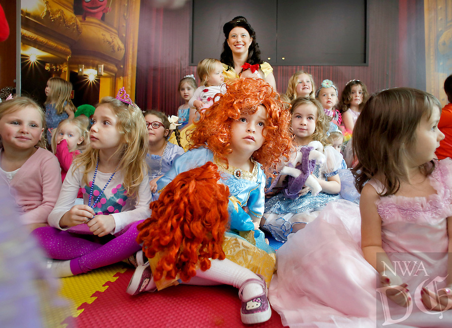 NWA Media/DAVID GOTTSCHALK - 3/14/14 - Elena Salamo (center foreground), 4, dressed as Princess Brave, sits with other children in costume as they pose with Autumn Mitchell (center rear), dressed as Princess Bell of Beauty and the Beast, Friday March 14, 2014 at the Fayetteville Public Library. The children were encouraged to dress as princes and princess as they participated in story time at the library with Little Giggles an organization based in Bentonville that focuses on creative play for children.