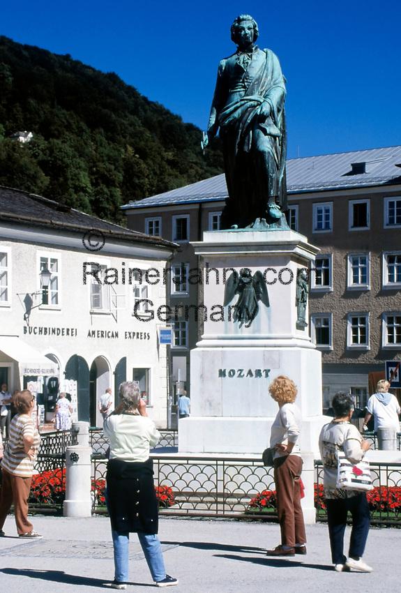 Oesterreich, Salzburger Land, Salzburg: Touristen beim obligatorischen Foto vor der Mozartstatue auf dem Mozartplatz   Austria, Salzburger Land, Salzburg: tourists taking photos of Mozart statue at Mozart Square