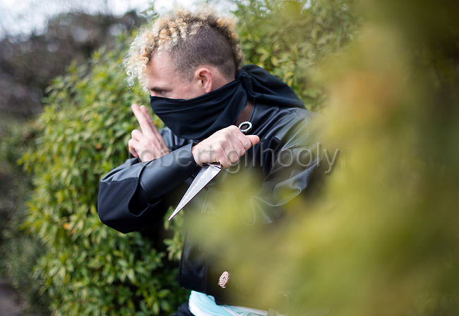 "Ninja Chris  ""Sora"" O'Neil gets ready to pounce in the grounds of Nagoya Castle, Aichi Prefecture Japan on Feb. 23, 2017. O'Neil is one of the eight ninja corps who roam the avenues of the castle and Nagoya Airport, jumping from behind trees and bushes to surprise visitors. ROB GILHOOLY PHOTO"