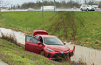 A Toyota Corolla sits in the ditch Thursday, March 19, 2020 next to Northbound Interstate 49 past Exit 81. Logan Mason, a University of Arkansas student from Bentonville, said he was driving the car Northbound when he came into heavy rain and hydroplaned. Mason said he was not injured. A second wreck happened at the same time on the Southbound side of the freeway, which caused lane closures. The National Weather Service issued a flash flood warning and tornado watch Thursday for Northwest Arkansas. Check out nwaonline.com/200320Daily/ for today's photo gallery.<br /> (NWA Democrat-Gazette/Ben Goff)