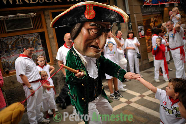 A young boy shakes hands with a man dressed as a giant during the giants and big heads parade of the San Fermin festival, on July 10, 2012, in the Northern Spanish city of Pamplona. The festival is a symbol of Spanish culture that attracts thousands of tourists to watch the bull runs despite heavy condemnation from animal rights groups. (c) Pedro ARMESTRE