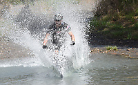 NWA Democrat-Gazette/FLIP PUTTHOFF <br /> BIG BIKE SPASH<br /> Victor Gurel of Springdale hits Lee Creek at high speed Saturday April 8 2017 during the Lee Creek Cannonball Big Splash Contest, part of the 29th annual Ozark Mountain Bike Festival at Devil's Den State Park. Contestants were judged on the size of their splash and style going into the water. Jeremiah &quot;Scratch&quot; Stone of Rogers won the contest. Festival events included guided mountain bike rides for all skill levels, clinics on riding technique, a poker run, bike games for kids and a cookout. The festival ends today with a guided ride at 10:30 a.m.