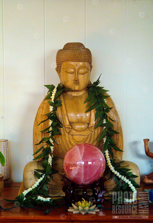 Wooden buddha statue wearing a Hawaiian lei with rose quartz crystal in healing room