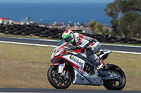Davide Giugliano (ITA) riding the Aprilia RSV4 1000 Factory (34) of the Althea Racing team exits turn 10 during a practise session on day two of round one of the 2013 FIM World Superbike Championship at Phillip Island, Australia. rounds turn 11 during a practise session on day two of round one of the 2013 FIM World Superbike Championship at Phillip Island, Australia.