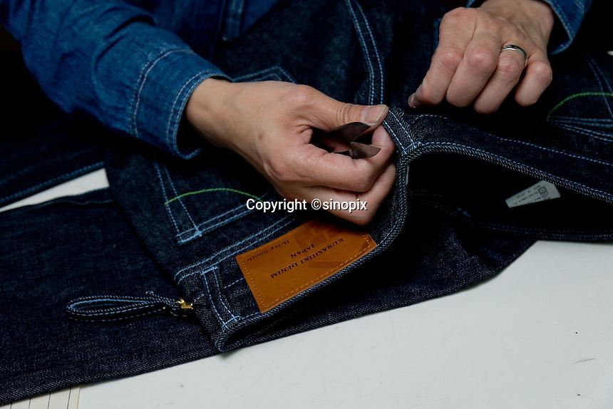 MAY 16, 2014 - KOJIMA, KURASHIKI, JAPAN: A worker inspects hand made ordered jeans at the Betty Smith's factory. (Photograph / Ko Sasaki)