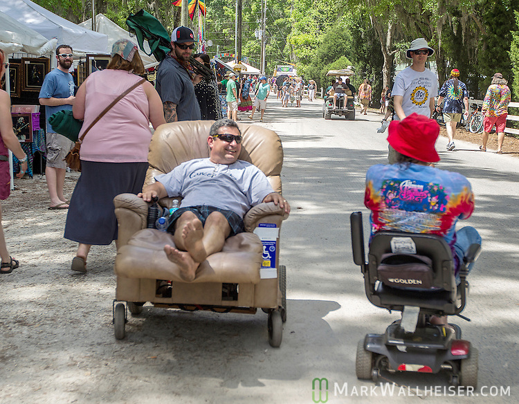 A battery operated easy chair (L) passes a mobility scooter Saturday during the Wanee Festival at the Spirit of the Swanee campground in Live Oak, Florida  April 12, 2014.