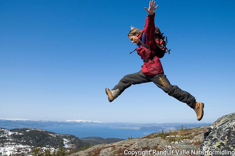 Våryr mann hopper på Gråkallen i Trondheim med Trondheimsfjorden i bakgrunnen ---- Man jumping