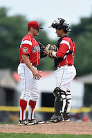 Batavia Muckdogs pitcher Connor Overton (56) talks with catcher Christopher Hoo (5) during the first game of a doubleheader against the Connecticut Tigers on July 20, 2014 at Dwyer Stadium in Batavia, New York.  Connecticut defeated Batavia 5-3.  (Mike Janes/Four Seam Images)