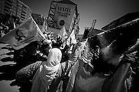 Le drapeau de droite est aux couleurs du Kurdistan, celui de gauche, également agité par les femmes, et celui d'une organisation civile pour la défense des droits des femmes et l'égalité homme-femme, dans un pays où elles sont discriminées. Au centre, sur l'immeuble, une publicité pour une machine à laver, tache domestique qui leur est dévolue.<br /> <br /> The flag on the right is the colors of Kurdistan, the one on the left, also agitated by women, is from a civil organization for the defense of women's rights and gender equality, in a country where they are discriminated against. In the center, on the building, an advertisement for a washing machine, domestic task entrusted to them.
