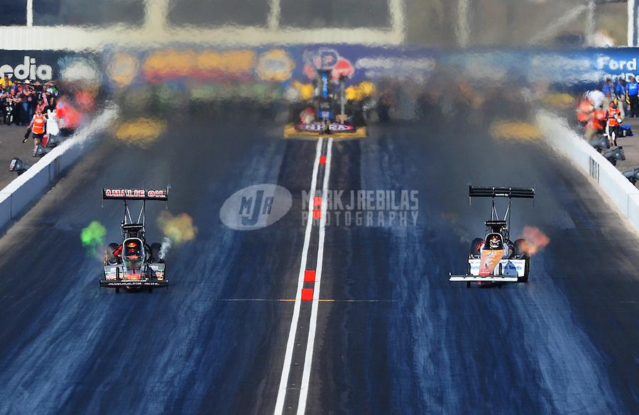 Feb. 18, 2012; Chandler, AZ, USA; NHRA top fuel dragster driver Terry McMillen (left) races alongside Clay Millican during qualifying for the Arizona Nationals at Firebird International Raceway. Mandatory Credit: Mark J. Rebilas-
