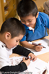 Education preschool 4 year olds art activity literacy one boy writing letters as another boy leans over to look at what he is doing vertical