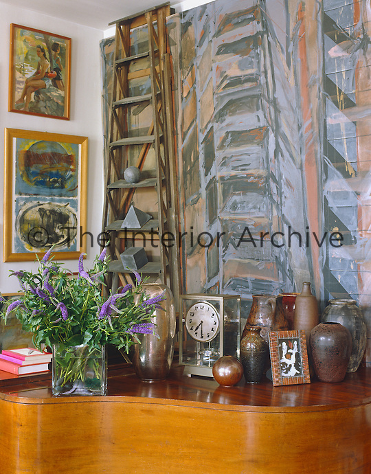 A monumental 3D canvas incorporating a ladder hangs behind the grand piano in the living room