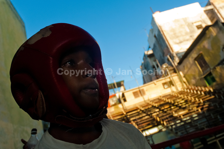 A young Cuban fighter wearing a headgear during a training session at Rafael Trejo boxing gym in Havana, Cuba, 13 February 2010. During the last 30 years Cuba has produced more World Champions and Olympic gold medallists in amateur boxing than any other country. Many famous fighters, who came out of Cuba, were training at Rafael Trejo boxing gym in their youth. This run down open air facility in the Old Havana is a place of learning and mastering the art of boxing by the old school style. Boys begin their training very young. As sports are given a high political priority in Cuba, all children are systematically encouraged to develop their skills. Those who succeed will become heroes of Cuban society.