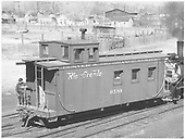 3/4 view of caboose #0584 at Montrose with engine #318 behind.<br /> D&amp;RGW  Montrose, CO  Taken by Richardson, Robert W. - 4/17/1952