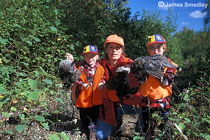 Mother with two daughters holding shot ruffed grouse