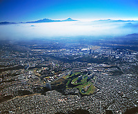 aerial photograph from Interlomas and Santa Fe districts in Mexico City to the Iztaccihuatl and Popcatepetl volcanoes.  The center of Mexico City is obscured by morning fog.