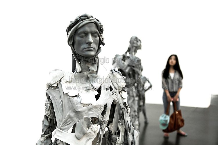 """A chinese woman stands staring the sculptures of  the series """"Selection from Venetians"""" by artist Pawel Althamer during an exhibition at UCCA Ullens Center for Contemporary Art in 798 Art Disctrict in Beijing, China, August 18, 2014. <br /> <br /> 798 Art District (Chinese: 798艺术区; pinyin: 798 Yìshùqū), or Dashanzi Art District, is a 50-year old decommissioned military factory buildings with unique architectural style. Located in Chaoyang District of Beijing, that houses a thriving artistic community. Since the beginning of 2000, 798 has become a centre for art galleries, artists's ateliers and contemporary arts exhibitions. The buildings are within alleys number 2 and 4 on Jiǔxiānqiáo Lù (酒仙桥路), south of the Dàshānziqiáo flyover (大山子桥).<br /> <br /> © Giorgio Perottino"""