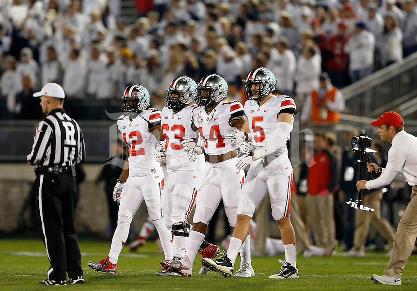 Ohio State Buckeyes cornerback Doran Grant (12), Ohio State Buckeyes defensive tackle Michael Bennett (63), Ohio State Buckeyes linebacker Curtis Grant (14) and Ohio State Buckeyes tight end Jeff Heuerman (5) come out for the coin toss before the NCAA Division I football game at Beaver Stadium in University Park, PA on October 25, 2014. (Columbus Dispatch photo by Jonathan Quilter)