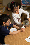 Preschool 3-4 year olds girl pouring milk for boy