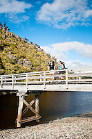 Two female trampers on a bridge at Three Mile Lagoon - Westland National Park, West Coast, New Zealand