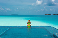 Maldives, Rangali Island. Conrad Hilton Resort. Woman in the infinty pool near the ocean. (MR)