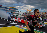 May 30, 2014; Englishtown, NJ, USA; Crew member Gary Pritchett runs alongside NHRA top fuel driver Steve Torrence during qualifying for the Summernationals at Raceway Park. Mandatory Credit: Mark J. Rebilas-