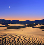 Early Morning Sunlight Merges With A Twilight Moon Over Sand Dunes And Mountains At Death Valley National Park, California, USA