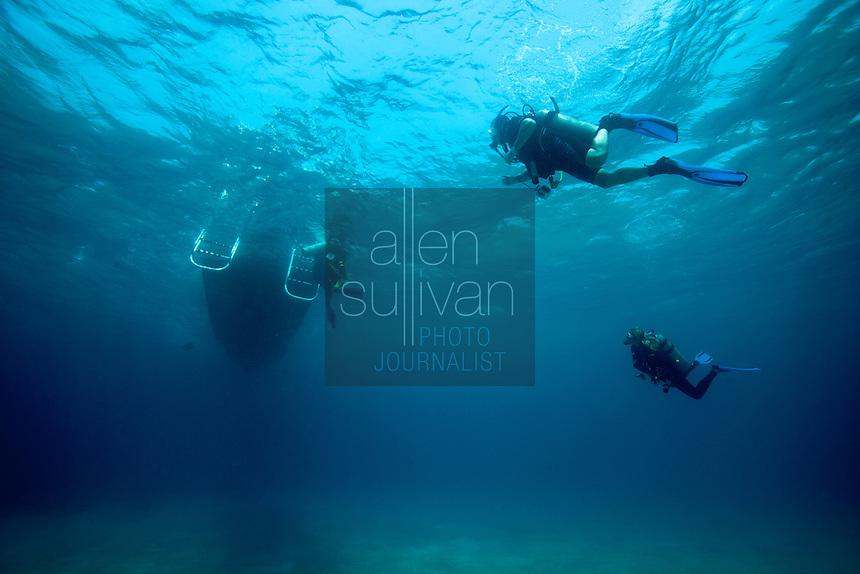 Scuba divers end their dive and board a boat; Roatan, Honduras.
