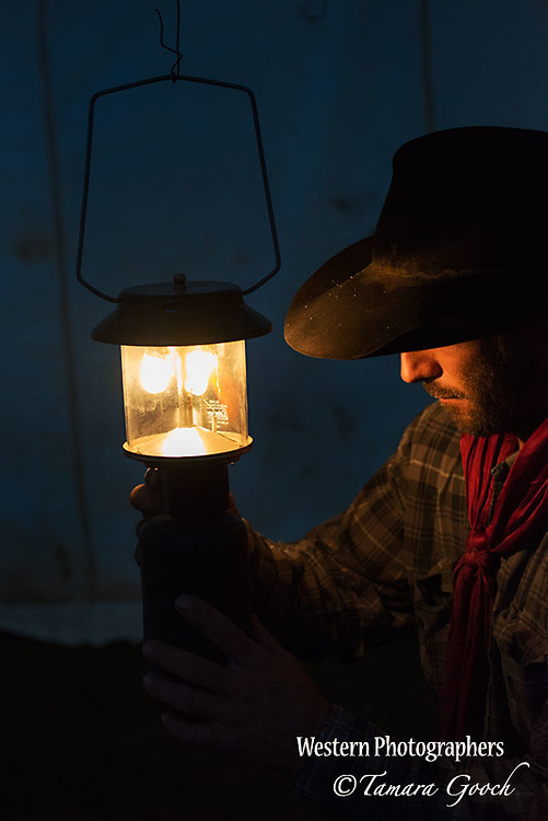 A photo of a cowboy lighting a lantern at night inside his tent. Cowboy Photos, riding,roping,horseback